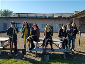 Leadership students take a well deserved break after cleaning up the courtyard area.