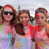 An image of three young female students covering in red chalk.