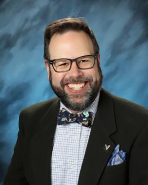 Mr. Windisch is smiling. He wears glasses and has a beard. He is wearing a collared shirt with a blue floral print bowtie.